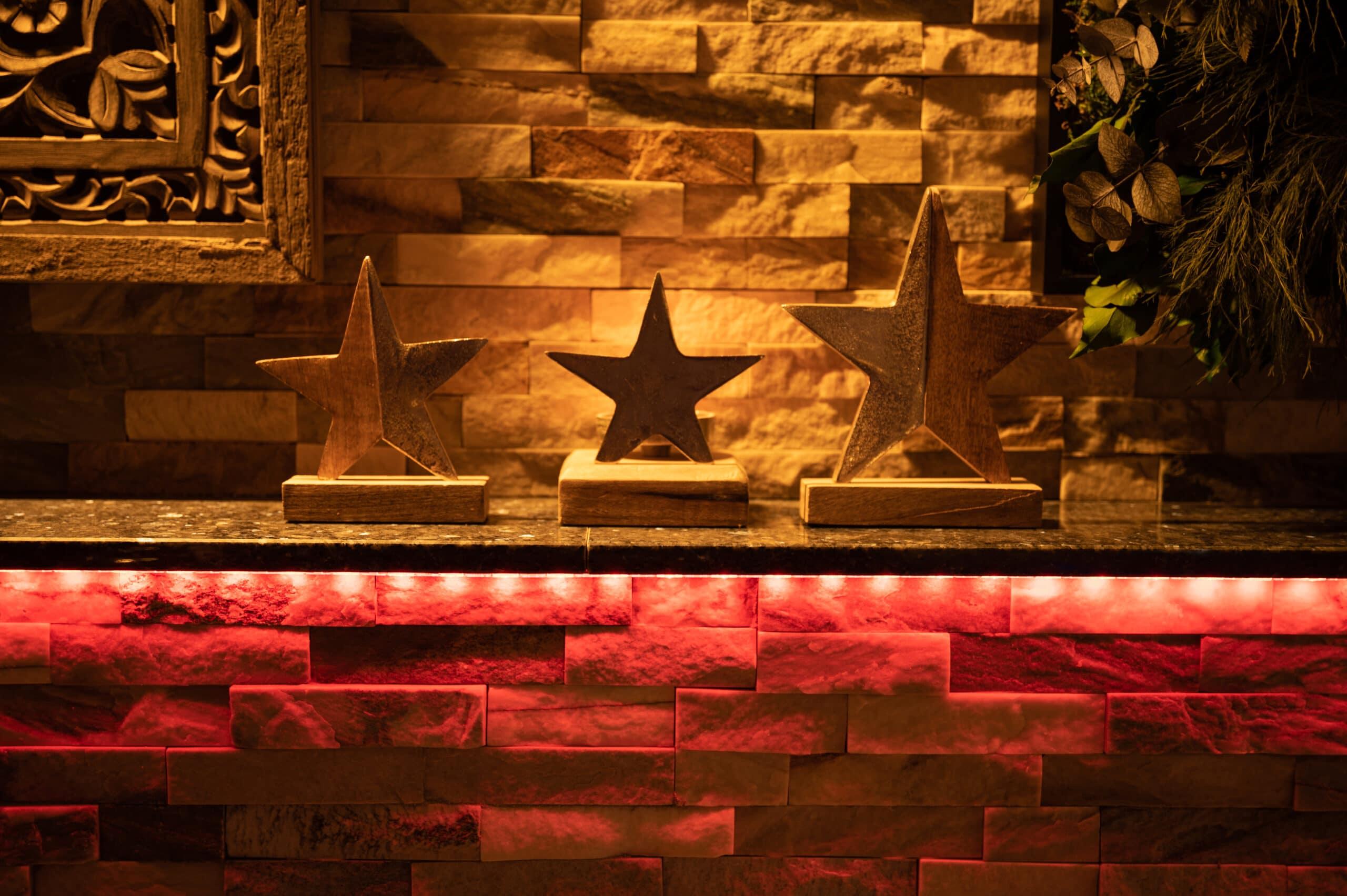 Sterne aus Holz und Metall vor unserer Natursteinwand.
